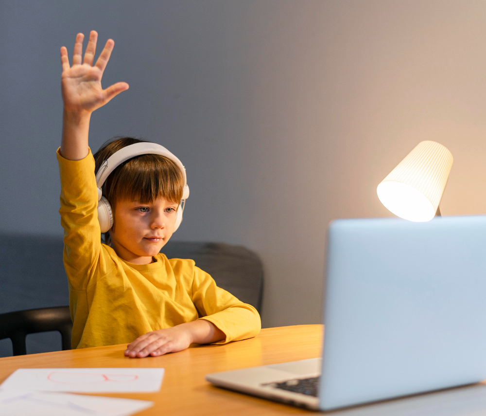 school boy yellow shirt taking virtual classes raising hand - Our mission - LRNG Academy - Shaping Boundless Generations - Online Tutoring | Online Learning | eLearning | Virtual School | Tutoring Service | Virtual Learning